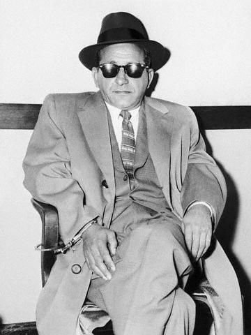 Giancana handcuffed in a chair.